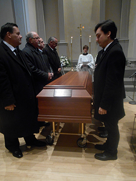 Pallbearers and priest with Stewart's casket.